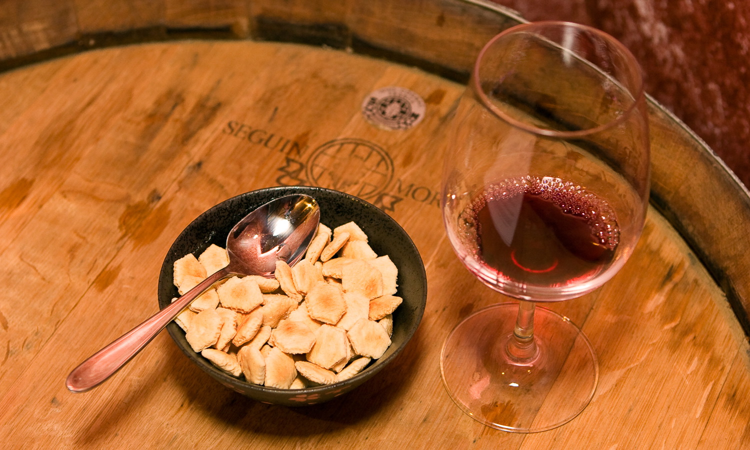 Oyster crackers and red wine on a wine barrel