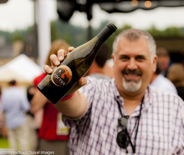 Randall Hopkins, co-owner of Corvus Cellars in Walla Walla, offers to share wine during the picnic portion at the 2013 Auction of Washington Wines in Woodinville, Wash.