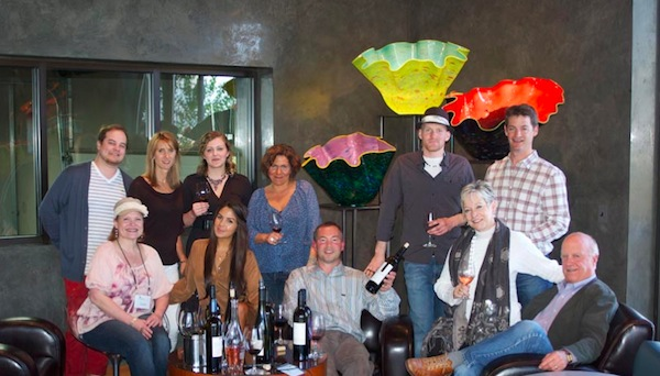Allen Shoup, seated at far right, and his Long Shadows team celebrate in their tasting room while surrounded by Chihuly glass pieces.