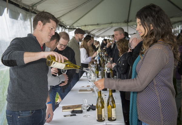 Paul Durant of Durant Vineyards pours for Melissa Burr of Stoller Family Estate during the grand tasting of the third annual Oregon Chardonnay Symposium on March 8, 2014 in Dayton.