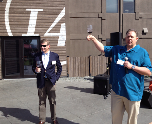 Keith Kenison, winemaker for 14 Hands, asks guests to raise their glasses as Ste. Michelle Wine Estates CEO Ted Baseler looks on as 14 Hands held its grand opening April 10, 2014, in Prosser, Wash. It is in the former Snoqualmie Winery facility. (Photo by Eric Degerman/Great Northwest Wine)