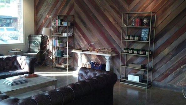 The Browne Family Vineyards tasting room interior features a herringbone timber accent wall, brown leather sofas and sitting areas with plaid wingback chairs.