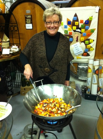 Ellena Conway prepares a dish for guests who are led into the barrel room.