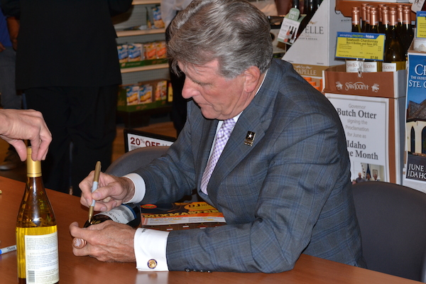 Idaho Gov. Butch Otter signs a bottle of Sawtooth wine during last year's event in Boise.
