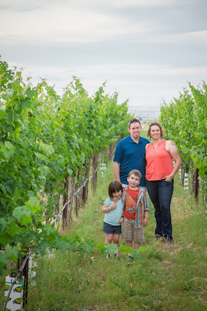 Kathryn House stands in Fraser Vineyard with her husband, Dr. Dan McClaskey, son Kellen, and daughter Mia.
