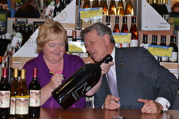 Idaho Gov. Butch Otter watches Ste. Chapelle winemaker Maurine Johnson as she adds her signature to a bottle signed by the governor during last year's event in Boise.