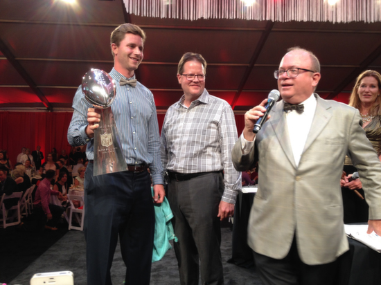 Steven Hauschka, placekicker for the defending Super Bowl champion Seattle Seahawks, is joined on stage, left to right, by Marty Clubb of L'Ecole No. 41 and auctioneers Fritz Hatton and Ursula Hermancinski on Saturday, Aug. 16, 2014. Hauschka's appearance with the Vince Lombardi Trophy was among the highlights at The Wine Gala, the finale for the Auction of Washington Wines. The three-day event has raised more than $30 million since its inception in 1988 for Seattle Children's Hospital and wine research at Washington State University.