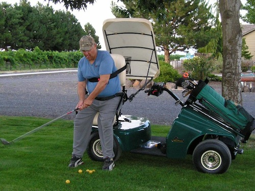 Paul Champoux uses a special single-rider golf cart that helps him stand and swing a golf club. He used it for the first time during this summer's Wine Cup. (Photo courtesy of Judy Champoux)