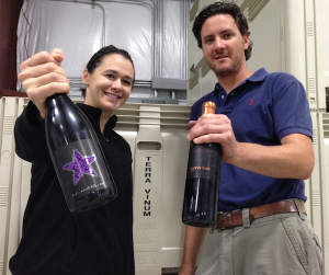 Amy Johnson presents a bottle of Purple Star Wines while Kyle Johnson holds a bottle of Red Mountain-based Native Sun.