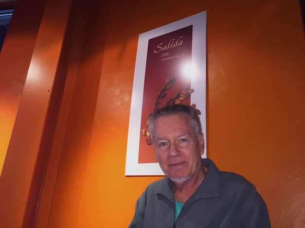 Doug McCrea poses under a poster of his 2006 Tempranillo, which marked his first vintage of working with the Spanish variety at his winery in Rainier, Wash
