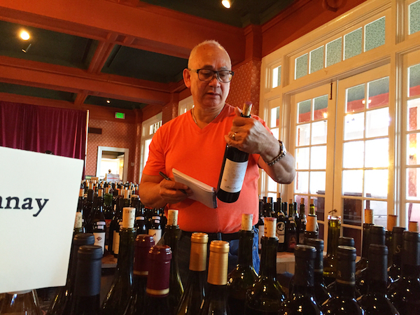 San Francisco native Wilfred Wong, chief storyteller for Wine.com and perhaps the United State's top wine judge, examines entries after the 2015 Great Northwest Wine Competition at the Columbia Gorge Hotel in Hood River, Ore.