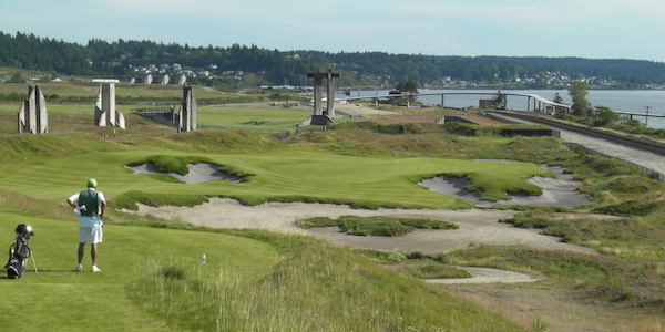 The Washington State Wine Commission tent along the 18th tee at the 2015 U.S. Open will be erected among the concrete columns that serve as a legacy of the cement plant at Chambers Bay in University Place, Wash. They are in the backdrop of this photo taken from the 17th tee.