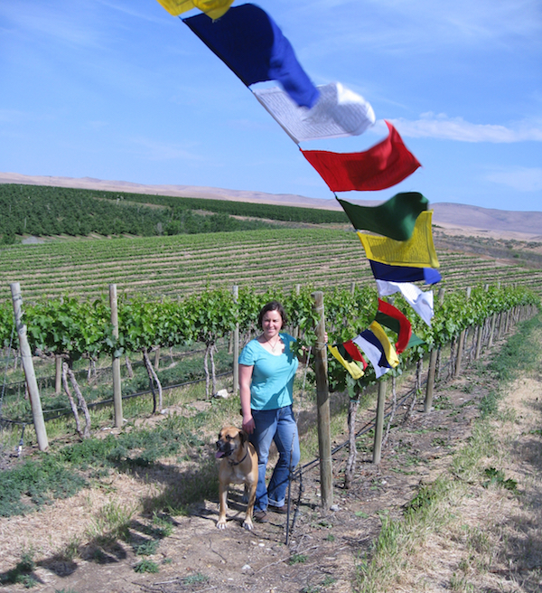 Cote Bonneville winemaker Kerry Shiels and her dog, Max, spend a moment under Nepal prayer flags, which she flies at her family's acclaimed DuBrul Vineyard in Washington's Yakima Valley. Shiels has established two crowd-sourcing efforts to raise money for her trekking guides in Nepal, whose homes were destroyed by the April 25, 2015 earthquake that Shiels experienced.
