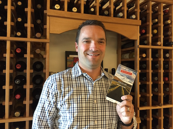 Chris Stone, vice president of communications and marketing for the Washington State Wine Commission, holds a copy of the commission's 2015 U.S. Open Tasting Guide.