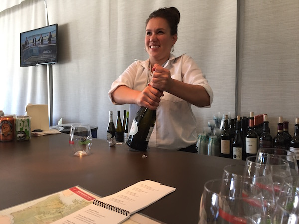 Jillian Copeland, a server at Chambers Bay, pops open a bottle of Michelle Sparkling Wine during U.S. Open at Chambers Bay Golf Course in University Place, Wash. (Photo by Eric Degerman/Great Northwest Wine)