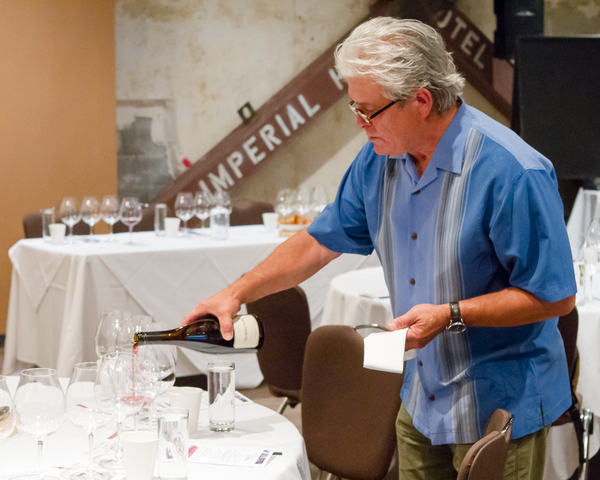Ken Wright, founding winemaker of Panther Creek Cellars, pours 20-year-old Pinot Noir made from Carter Vineyard, during a celebration at the Imperial Hotel in Portland. (Photo by Chris Bidelman/Courtesy of Bacchus Capital Management)
