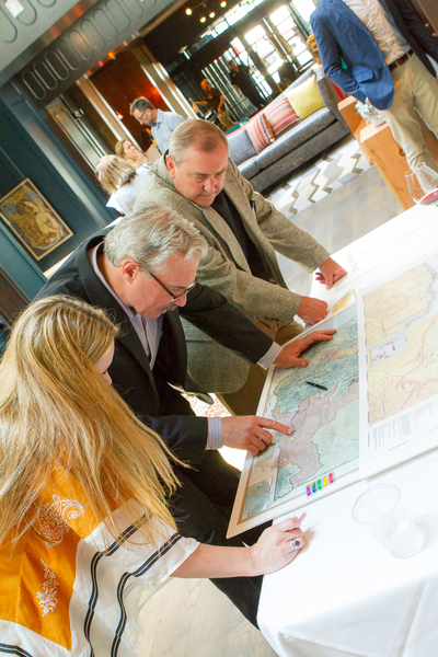 David West, the first employee at Panther Creek Cellars, winemaker Tony Rynders, and Christie Shertzer, hospitality manager at Panther Creek, look over a map of the Willamette Valley. (Photo by Chris Bidelman)