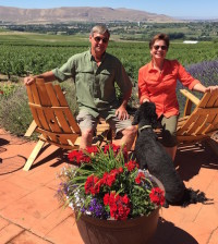 Larry Pearson and his wife, Jane, entertain Hugo, the youngest of their two standard poodles, on their Red Mountain patio at Tapteil Vineyard and Winery in Benton City, Wash.