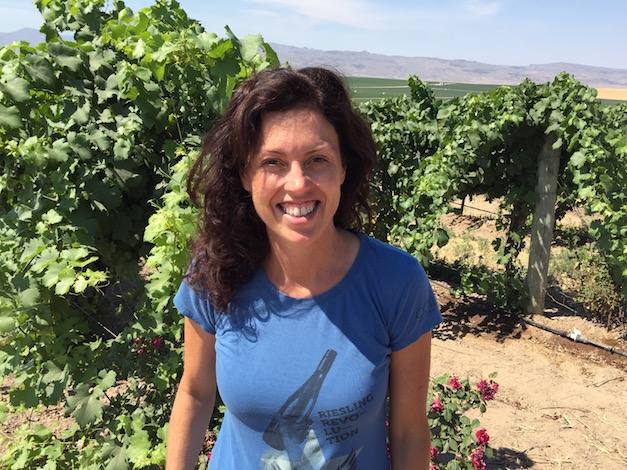 Leslie Preston of Coiled Wines stands in Sawtooth Vineyard with Skyline Vineyard — Idaho's largest site for wine grapes — in the background.