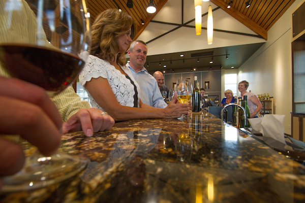 A group of visitors relaxes at the bar in the Walter Clore Wine and Culinary Center tasting room in Prosser, Wash. (Photo by Pixelsoft Films/courtesy of the Clore Center)