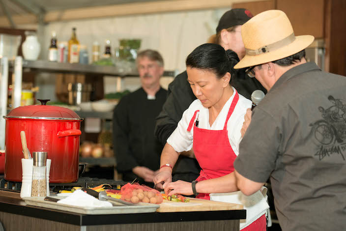 """Lisa Nakamura of Gnocchi Bar in Seattle prepares a dish for the Taste of Tulalip Challenge while being interviewed by Thierry """"Chef in the Hat"""" Rautureau of Luc and Loulay Kitchen and Bar"""