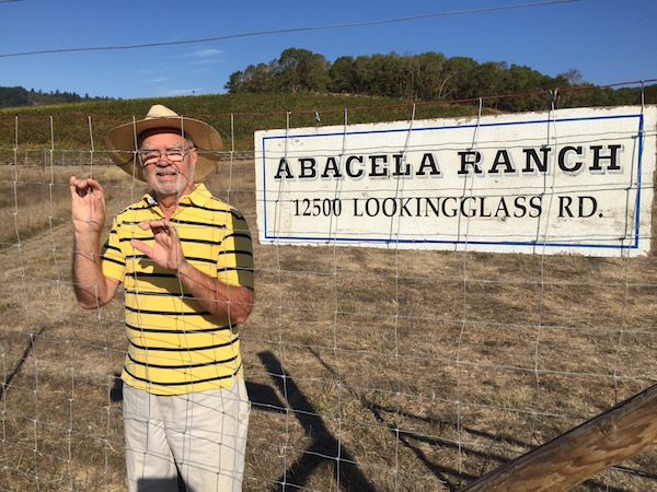 Earl Jones, founding winemaker and co-owner of Abacela in Roseburg, Ore., poses with the original sign for his winery and vineyard project, which he launched in 1995. (Photo by Eric Degerman/Great Northwest Wine)