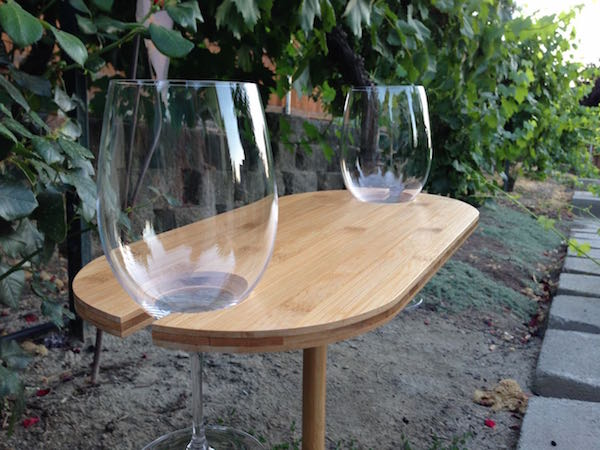 Bamboo Wine Table from Uncommon Goods holds two glasses of wine.