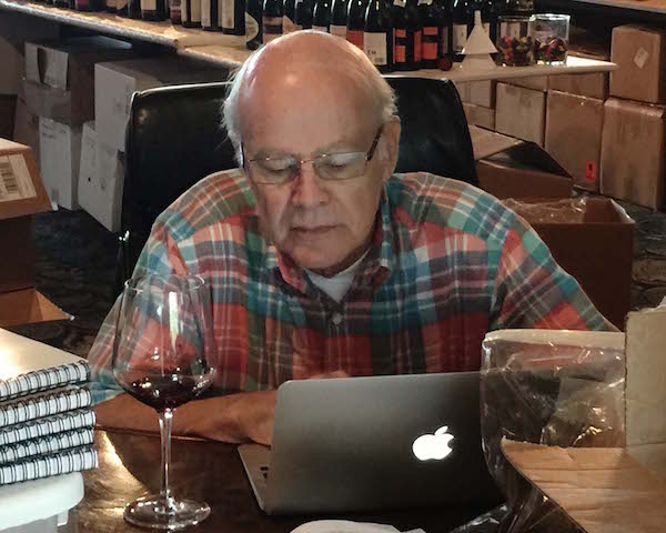Ken Robertson, chief of judges at the 2015 Great Northwest Invitational Wine Competition, reviews a wine moments after it was awarded a gold medal by one of the five judging panels at the historic Columbia Gorge Hotel in Hood River, Ore.