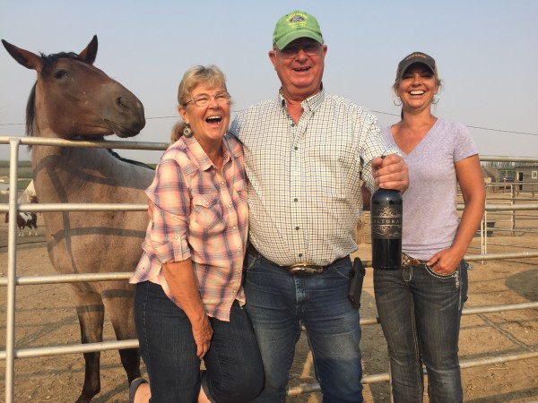 A rescue horse provides some morning levity for Pepper Fewel, her husband, Terry, and daughter Tiffany at Cherry Wood Bed Breakfast and Barn in Zillah, Wash. Terry holds a bottle from nearby Cultura Winery, which is owned by winemaking son, Tad.