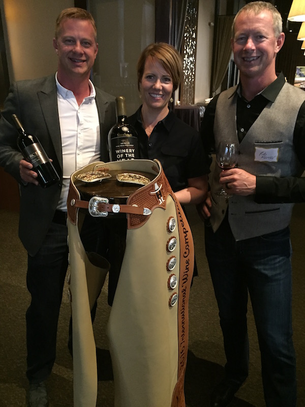 Will Mercer, winemaker Jessica Munnell, and owner Rob Mercer celebrate some of their recent successes, which include Wine Press Northwest 2016 Washington Winery of the Year and a pair of championship chaps from the Houston Livestock Show and Rodeo International Wine Competition. (Photo by Eric Degerman/Great Northwest Wine)