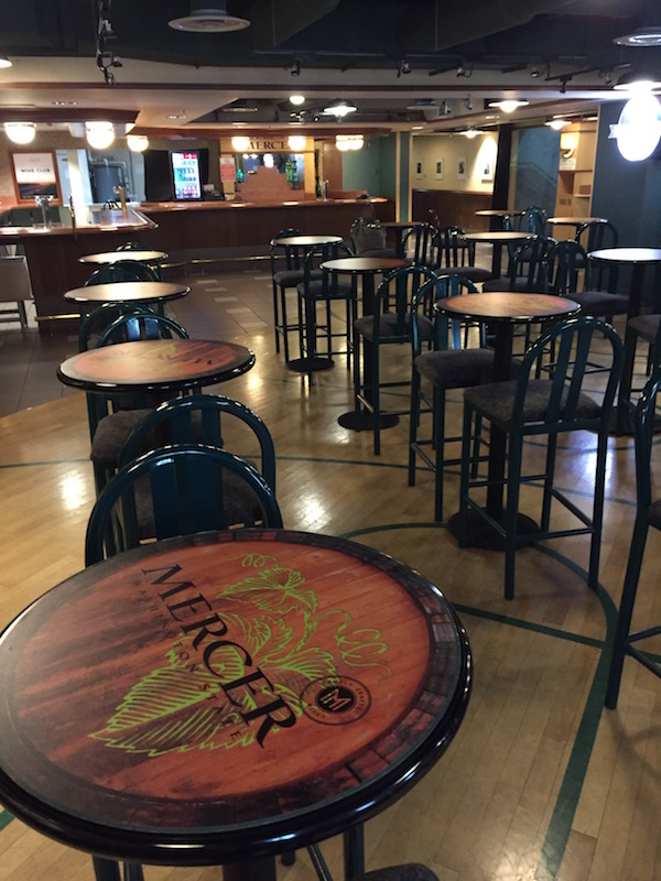 The Mercer Estates Wine Bar at KeyArena includes barrel-themed bistro tables across a floor reminiscent of a basketball court.