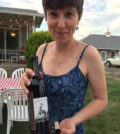 Coco Umiker, winemaker for Clearwater Canyon Cellars, celebrates the 100th anniversary of her family farm with a bottle of the 2013 Heritage Series Ralph E. Nichols Red Wine, named for her late grandfather. (Photo by Eric Degerman/Great Northwest Wine)