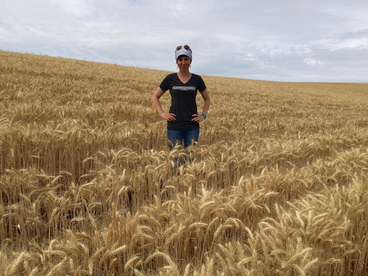 Coco Umiker stands in a wheat field on the Nichols Family Farm in Lewiston, Idaho, a 57-acre century farm that now includes Umiker Vineyard and its 6.5 acres of wine grapes.
