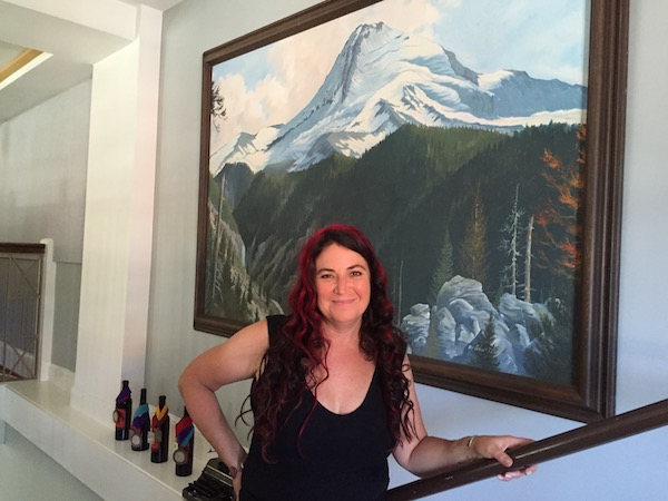 Rachael Horn of AniChe Cellars stands below a painting of Mount Hood, a work displayed on the mezzanine level of her new tasting room and art gallery inside the Butler Banking Co., Building in Hood River, Ore.