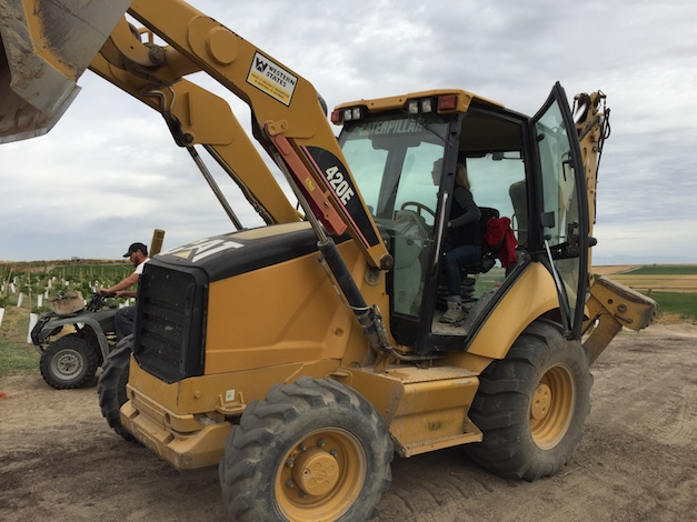 Sydney Nederend operates a Caterpillar while working on an estate planting for Scoria Vineyards and Winery. (Photo by Eric Degerman/Great Northwest Wine)